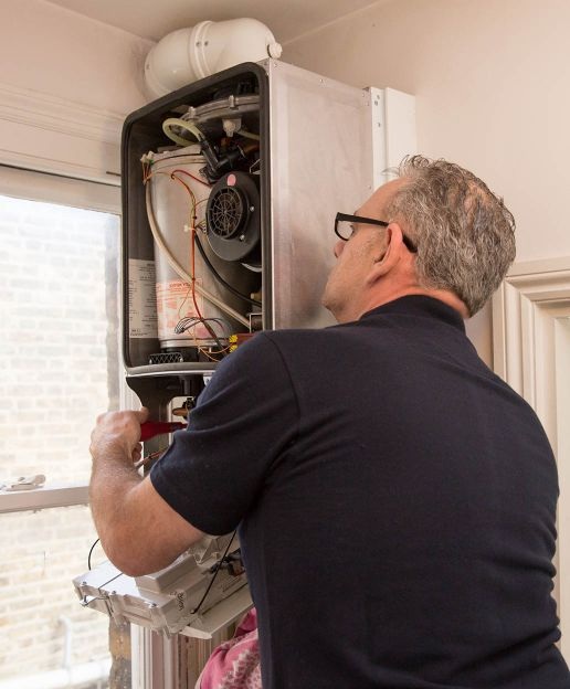 Gas and heating engineer repairing a boiler in London